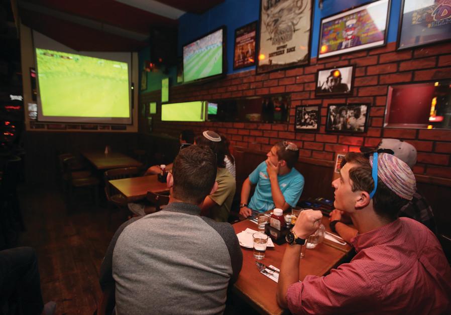 FANS SITTING in Mike's Place in Tel Aviv watch Russia's win over Saudi Arabia in last night's openin