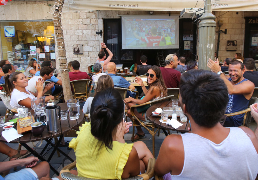 Fans sitting in a bar in Jerusalem watching the first game of the 2018 World Cup