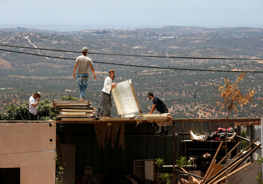Jewish settlers dismantle parts of a structure during the eviction of buildings that an Israeli cour