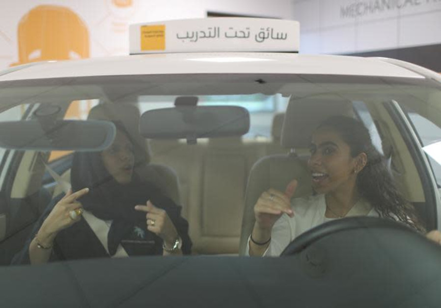 A driving instructor teaches trainee Maria al-Faraj (R) during a driving lesson