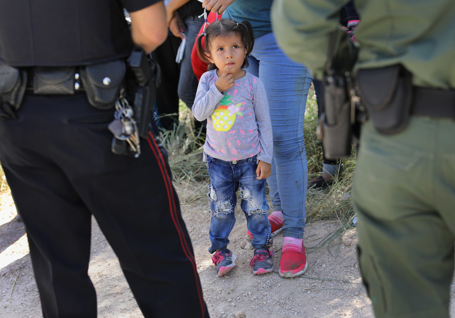 A Mission Police Dept. officer (L), and a US Border Patrol agent watch over a group asylum seekers