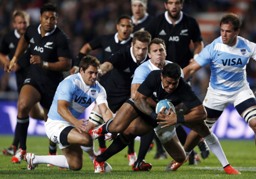 Malakai Fekitoa (C) of New Zealand's All Blacks is tackled by Argentina's Juan Imhoff (C, back) and