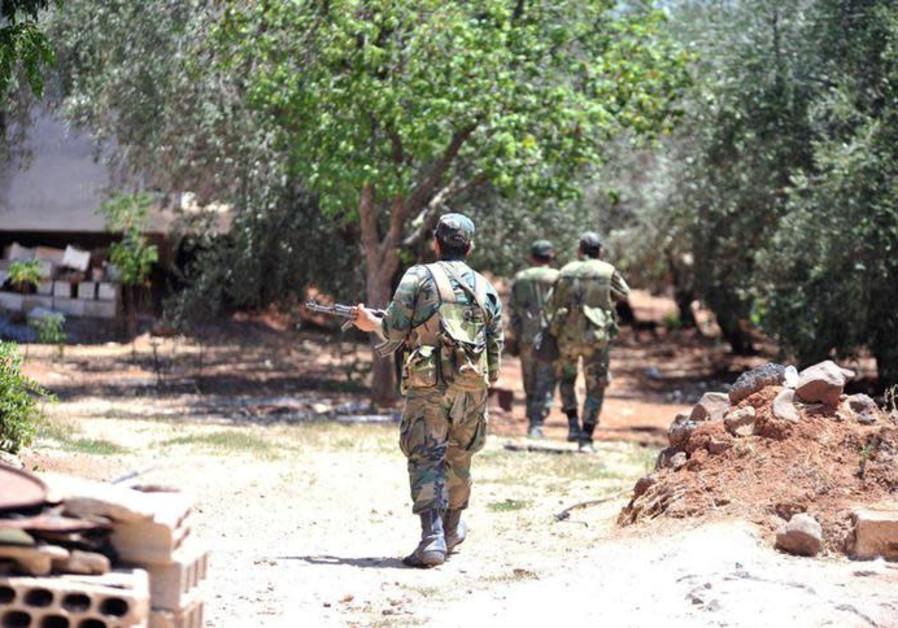 Forces loyal to Syria's President Bashar al-Assad walk in al-Ghariya al-Gharbiya in Deraa province