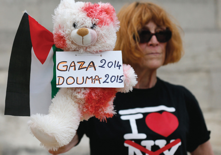 A WOMAN holds a stuffed bear, covered in fake blood, and a Palestinian flag to protest the 'Tel Avi
