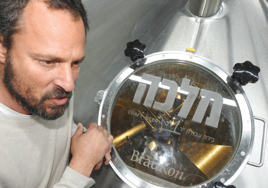 ASSAF LAVI inspects the brewing kettle in the new Malka Brewery in Tefen