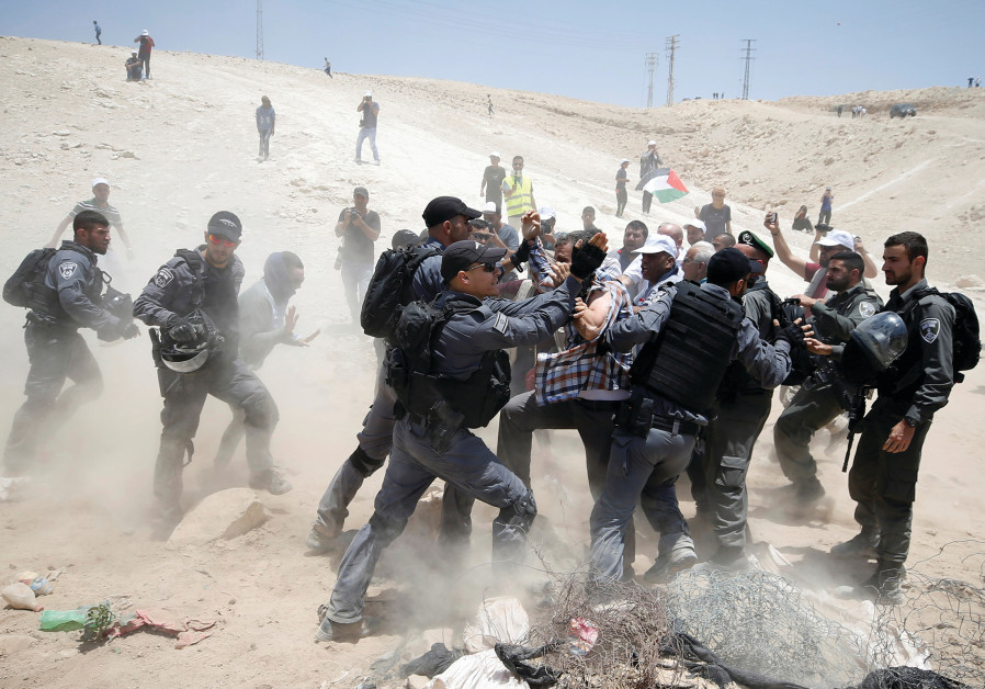 ISRAELI POLICEMEN scuffle with Palestinians in Khan al-Ahmar yesterday.