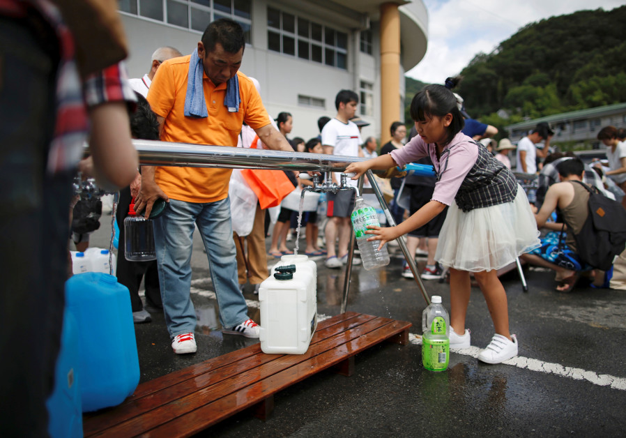 Local residents receive emergency water supply near a flooded area at Mihara Daini, July 2018