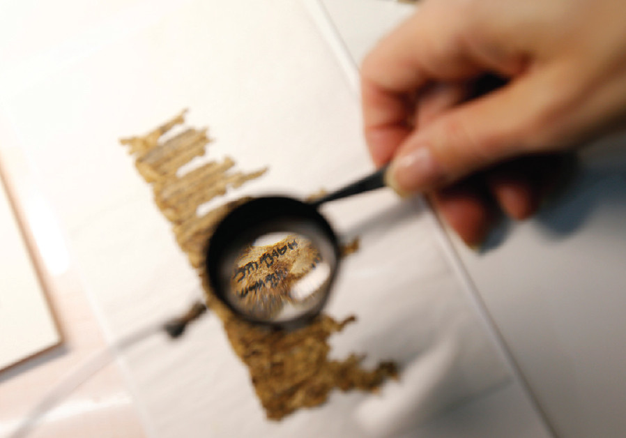 A restorer works on a fragment of the Dead Sea Scrolls in a laboratory at the Israel Museum in Jerus