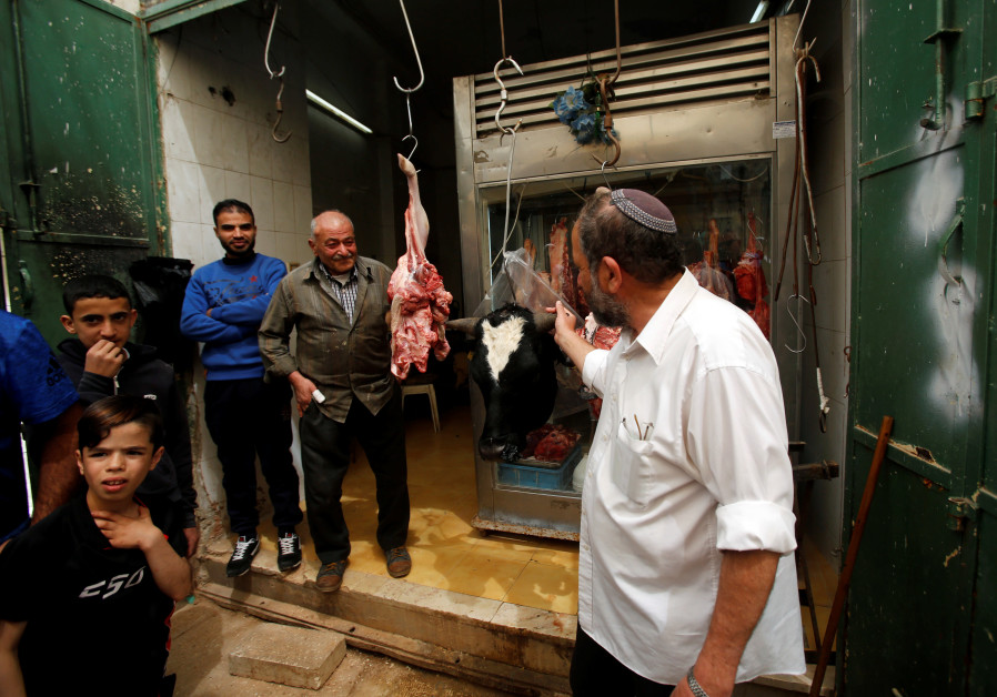 A Jewish man looks at meat at Palestinian butcher's shop in Hebron, in West Bank, 2018.