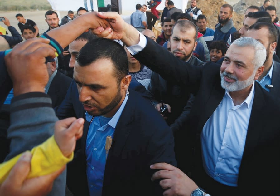 HAMAS CHIEF Ismail Haniyeh shakes hands with a boy during a protest at the Gaza border on April 9, 2