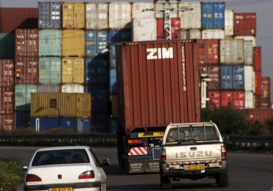Cars drive behind a truck transporting a Zim container just outside Israel's port of Ashdod February