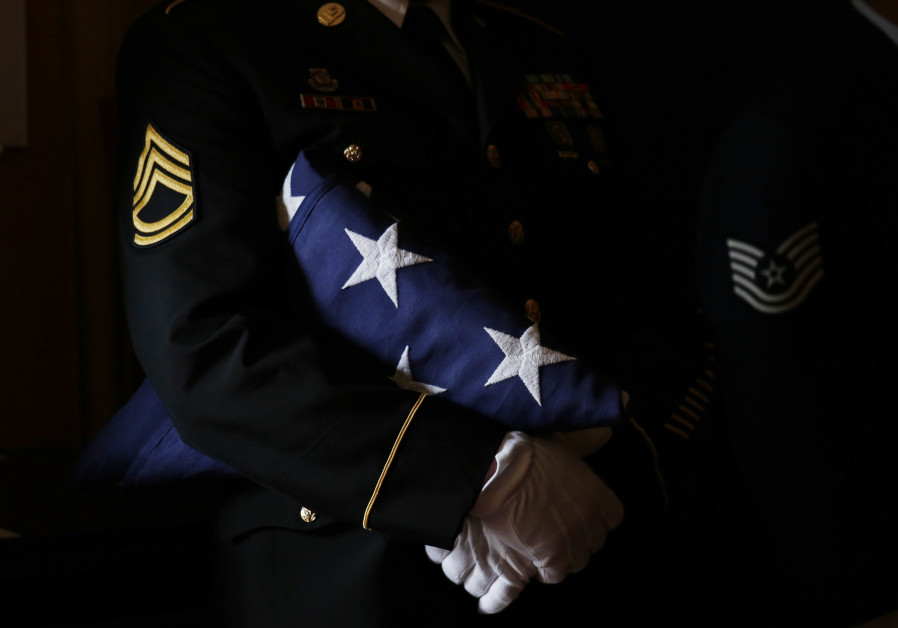 A member of a US military color guard holds a folded American flag during a military funeral