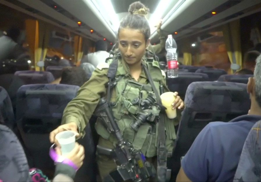 An Israeli solider hands out water on a bus, during the Syria Civil Defence, also known as the White