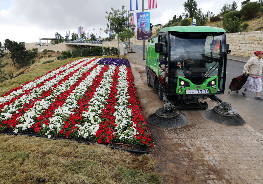 A street sweeper cleans sidewalk next to a flower bed in shape of U.S. flag, near location of new U.