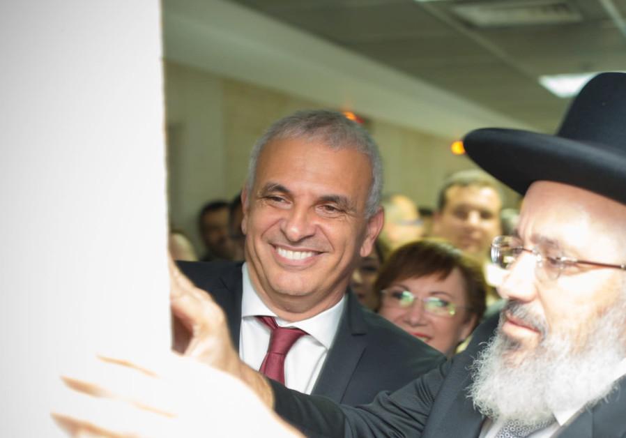 Finance Minister Moshe Kahlon affixes a mezuza at Kulanu party's new Tel Aviv headquarters