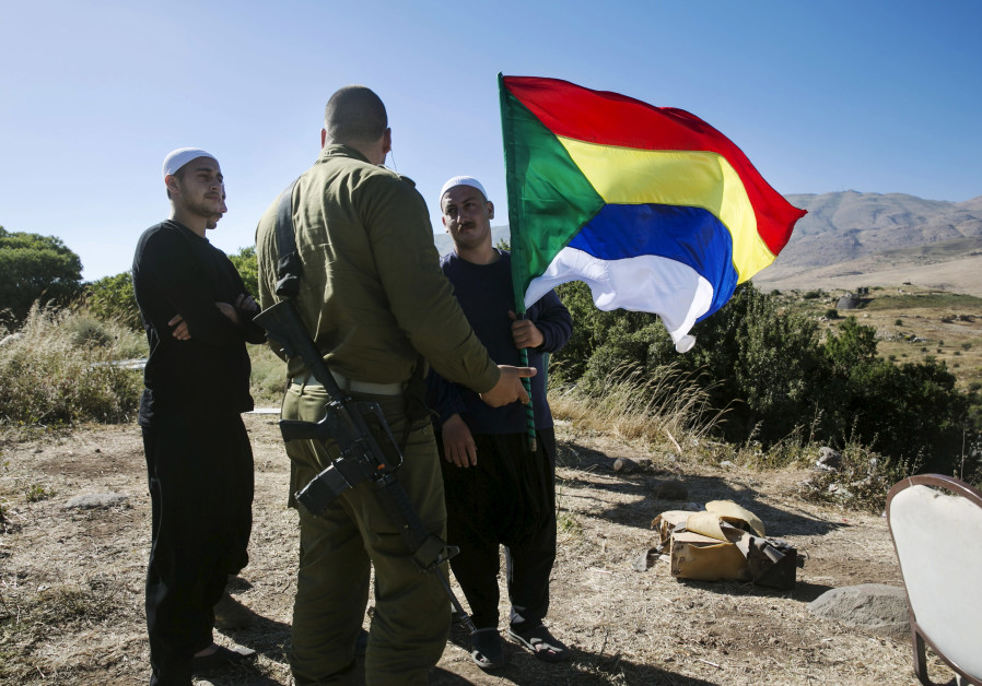 A member of the Druze community holds a Druze flag as he speaks to an Israeli soldier near the borde