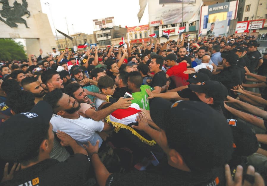 PROTESTERS ARE pushed back by Iraqi security forces during a protest at Tahrir Square in Baghdad, Ju