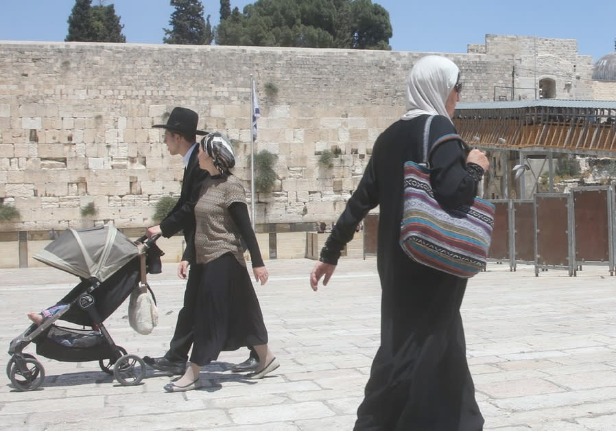 AN ARAB woman walks past a Jewish couple at the Western Wall