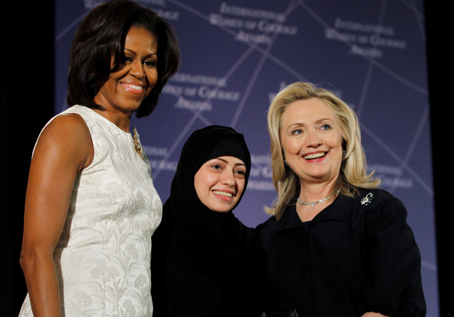 US Secretary of State Hillary Clinton and First lady Michelle Obama (L) congratulate Samar Badawi of