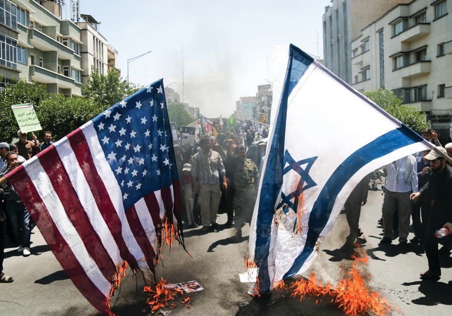 IRANIANS BURN US and Israeli flags during a protest in Tehran in June