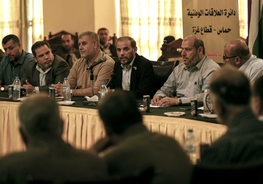 Hamas officials Husam Badran (C) and Khalil al-Hayya (2nd-R) attend a meeting
