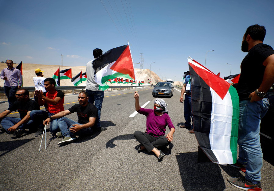 Demonstrator holds Palestinian flag during support rally of Khan al-Ahmar residents: West Bank, 2018