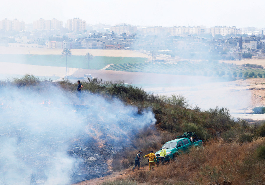 People are seen near Kibbutz Nir Am during a fire in an area where Palestinians in Gaza have been ca
