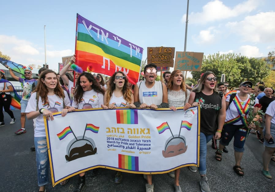 MARCHERS TAKE part in the Jerusalem Pride Parade this past Sunday, as a sign in the background procl