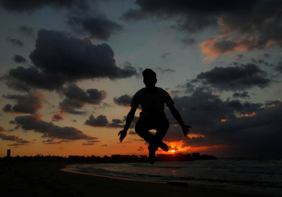 A Palestinian man jumps during the last sunset in 2016 at a beach in the northern Gaza Strip Decembe