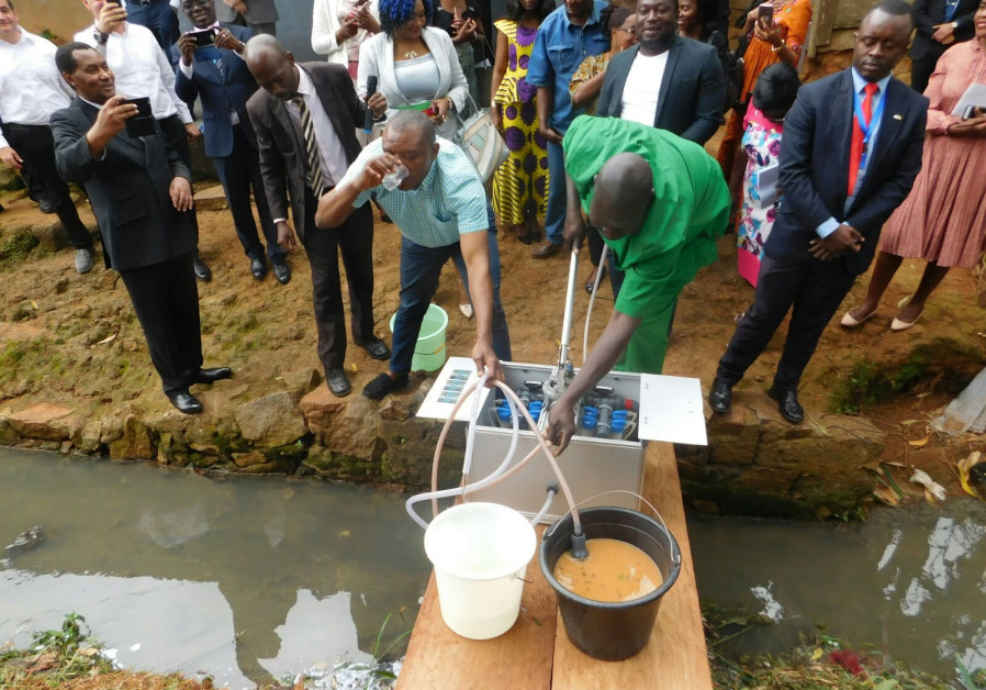 A demonstration of the NUF purification system in Cameroon to government officials, local journalist