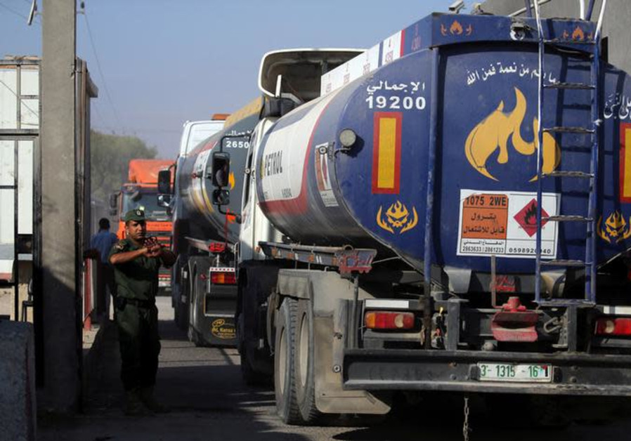 A member of Palestinian security forces gestures as a fuel tanker arrives at Kerem Shalom crossing
