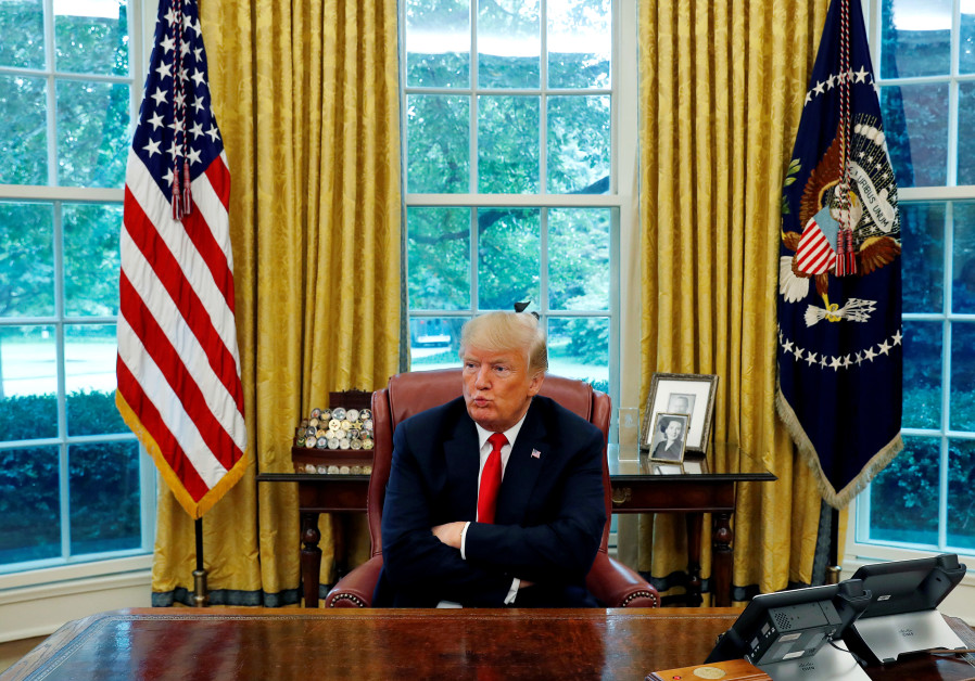 US President Donald Trump reacts to a question during an interview with Reuters in the Oval Office o
