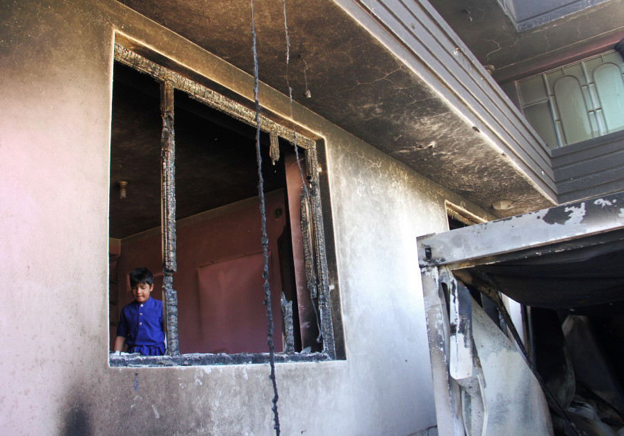An Afghan boy is seen inside a burnt building after a Taliban attack in Ghazni city, Afghanistan Aug