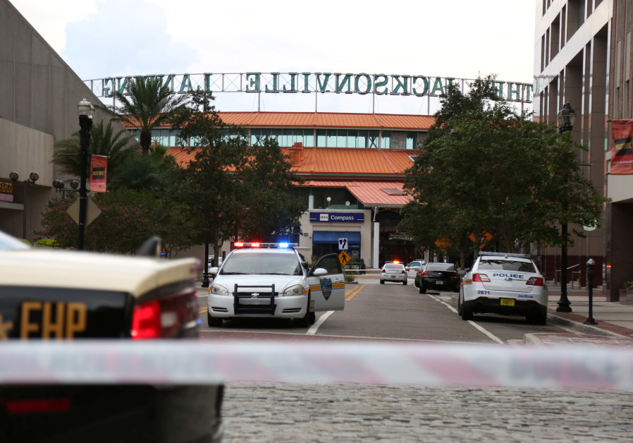 Police officers cordon off a street outside The Jacksonville Landing after a shooting during a video