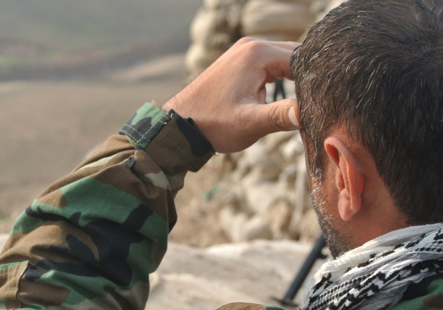 A PAK member looks out over a frontline during the war on ISIS in Iraq in 2016.