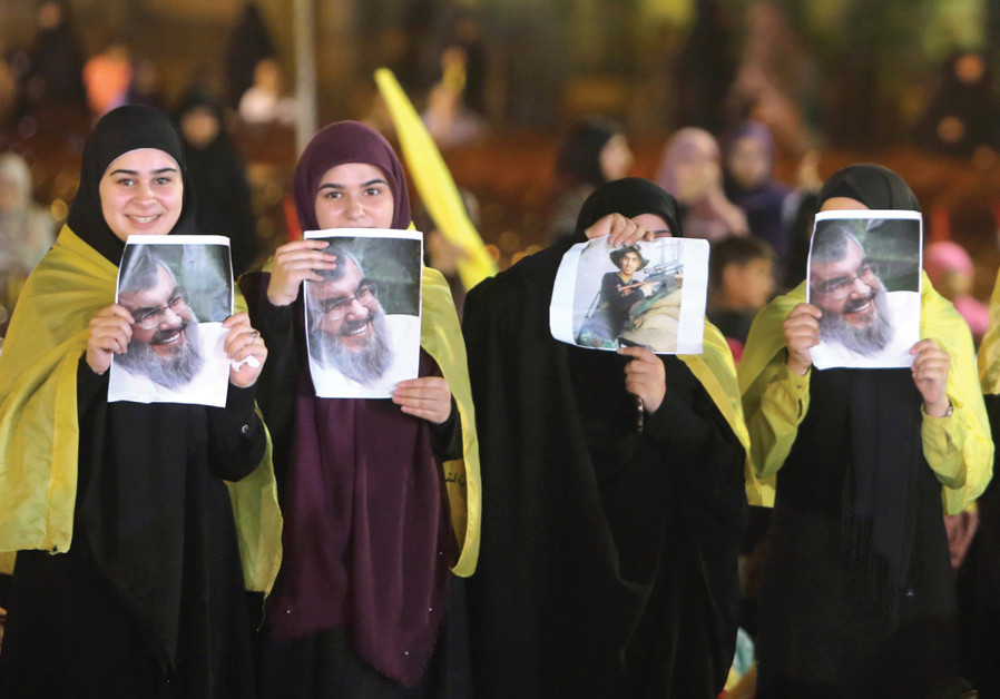 FEMALE SUPPORTERS display pictures of Hezbollah leader Sayyed Hassan Nasrallah as he remotely delive