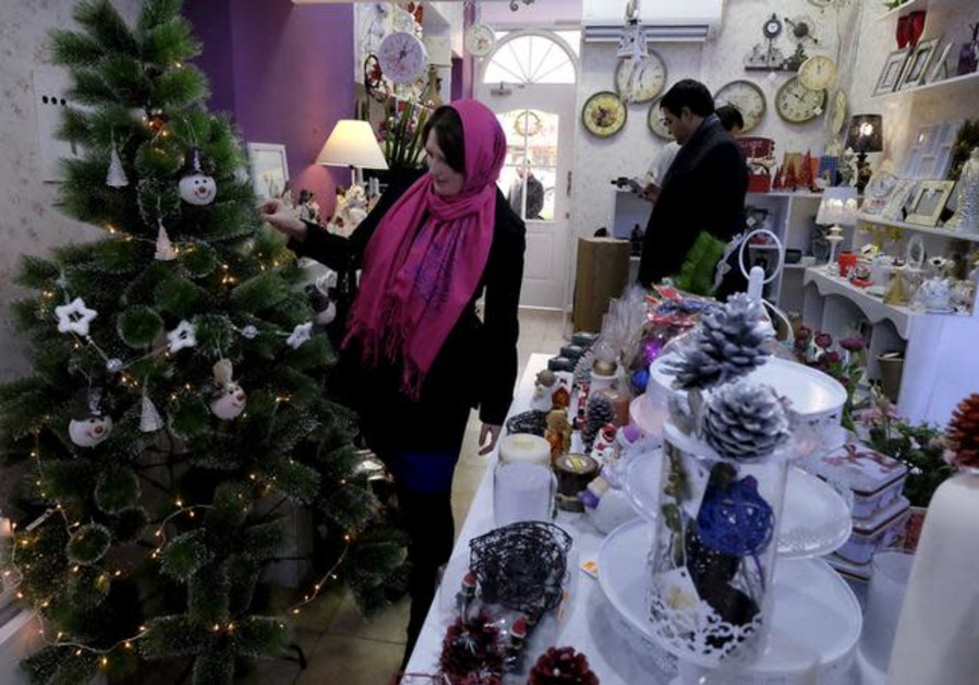 An Iranian Christian woman looks at a Christmas tree at a shop in central Tehran December 23, 2015