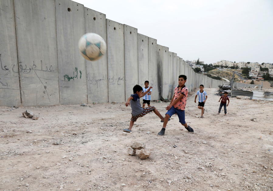 Nassim Ammour, 11, scores a goal as he plays with friends next to the Israeli barrier in Shuafat
