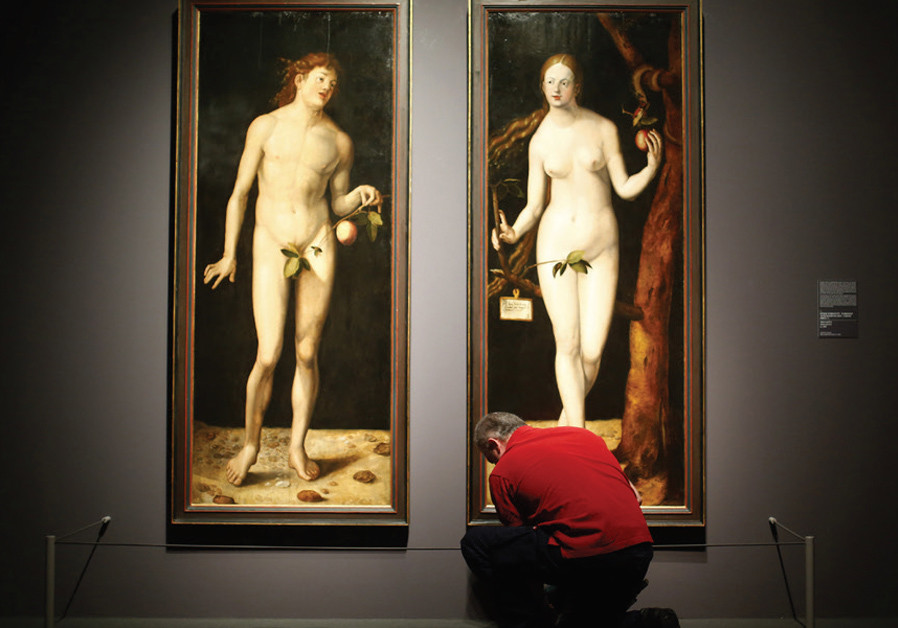 A museum worker cleans the floor in front of the paintings 'Adam' and 'Eve' by Hans Baldung Grien, t
