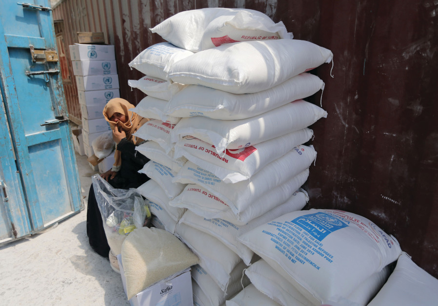 A PALESTINIAN woman sits next to bags of UNRWA flour