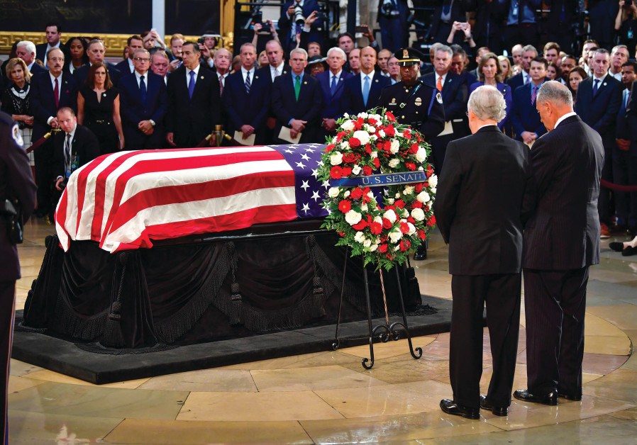 JOHN MCCAIN'S casket rests in front of mourners