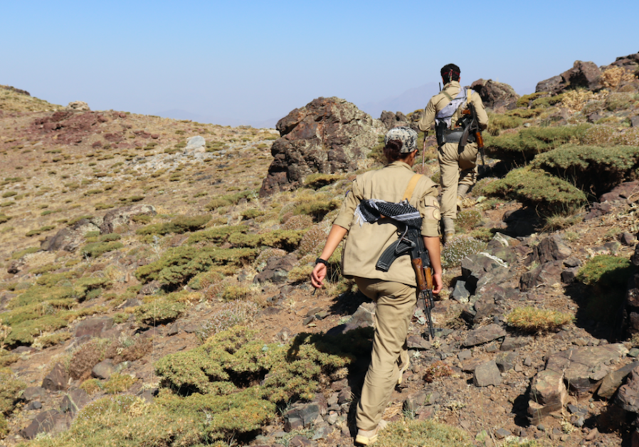 KURDISH MEMBERS of Democratic Party of Iranian Kurdistan hike through mountains from Iraq to Iran.