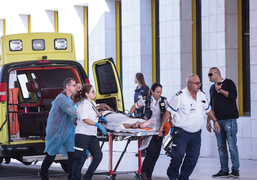 Assuta staff rush a patient to the hospital through its emergency entrance