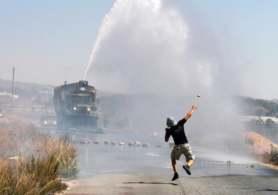 A PALESTINIAN demonstrator hurls a stone as an Israeli truck fires a water cannon during clashes.