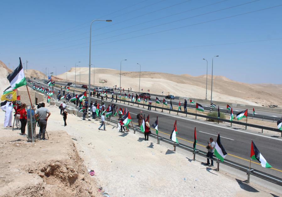 Protestors raising Palestinian flags at Bedouin village Khan al-Ahmar designated for demolition, Sep