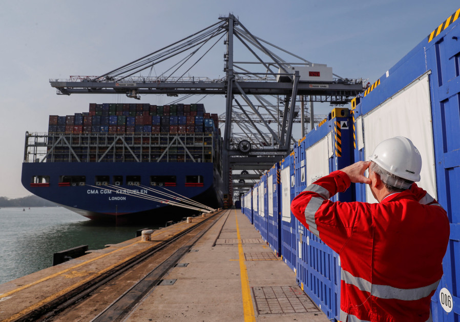Freight containers are seen on a freight container ship as a worker looks on at DP World