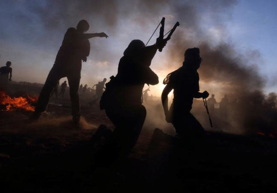 Palestinians hurl stones at Israeli troops during a protest at the Israel-Gaza border fence