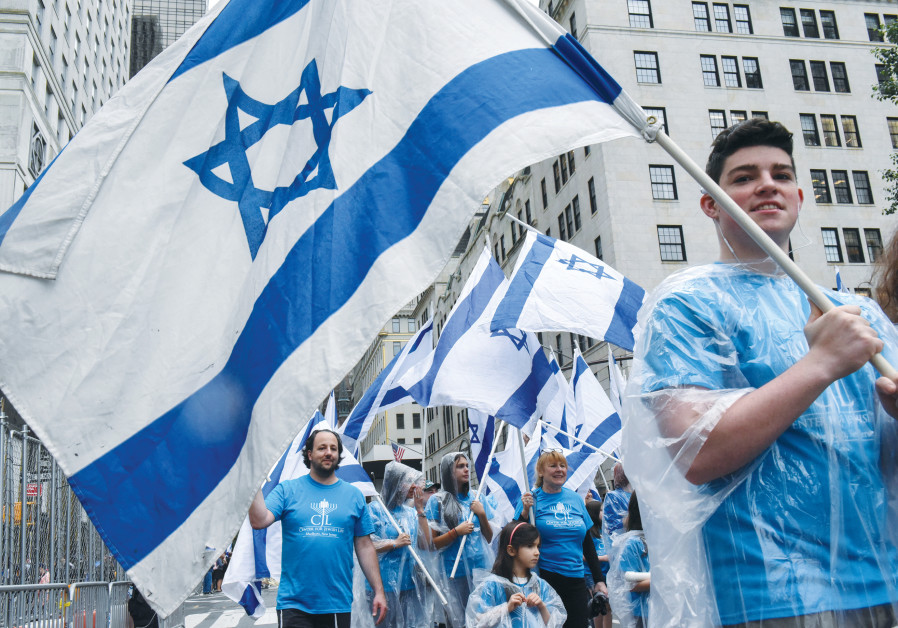 Participants carry Israeli flags at the 'Celebrate Israel'' parade along Fifth Avenue in New York