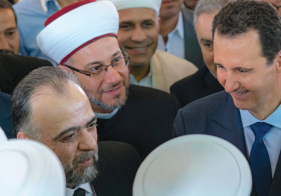 SYRIAN PRESIDENT Bashar Assad greets supporters during Eid al-Adha prayers at a Damascus mosque on A