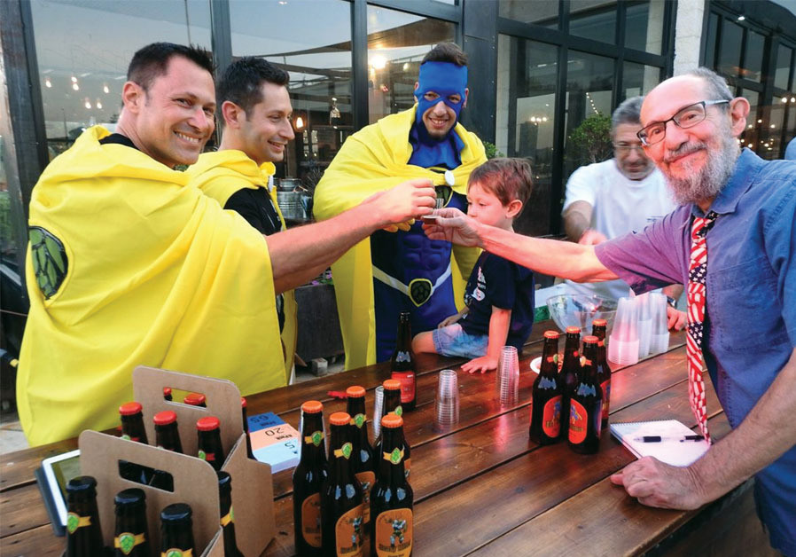 THE WRITER (right) raises a glass with 'superheroes' from Six Pack Brewing, at a recent craft beer f